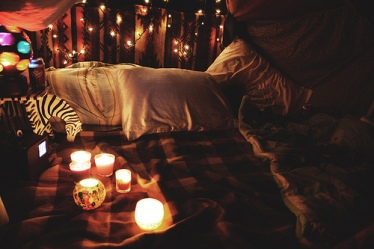 photo of the inside of a pillowfort lit by string lights and candles